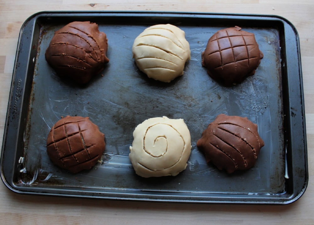 Unbaked conchas on a baking sheet.