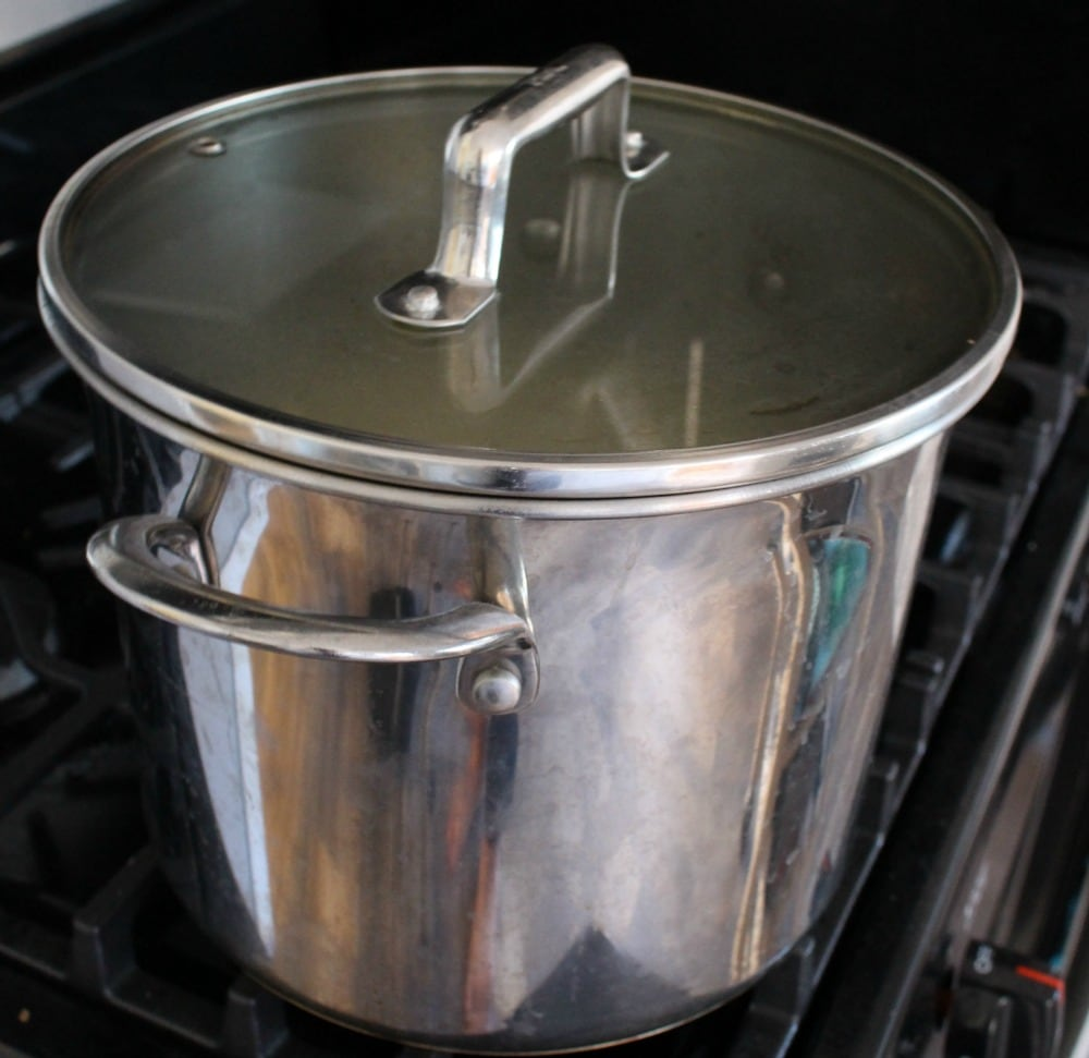 A large stock pot of chicken pozole cooking on the stove.