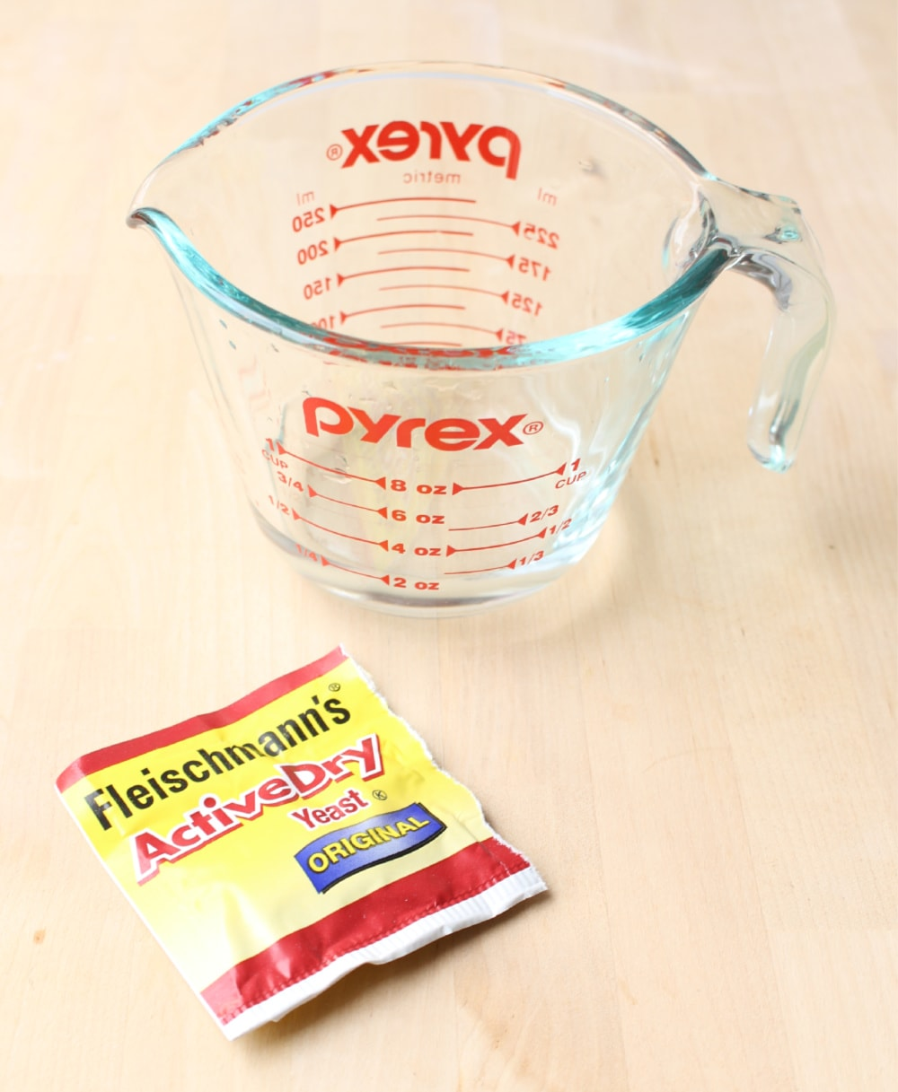 A package of yeast with a measuring cup on a wooden surface.