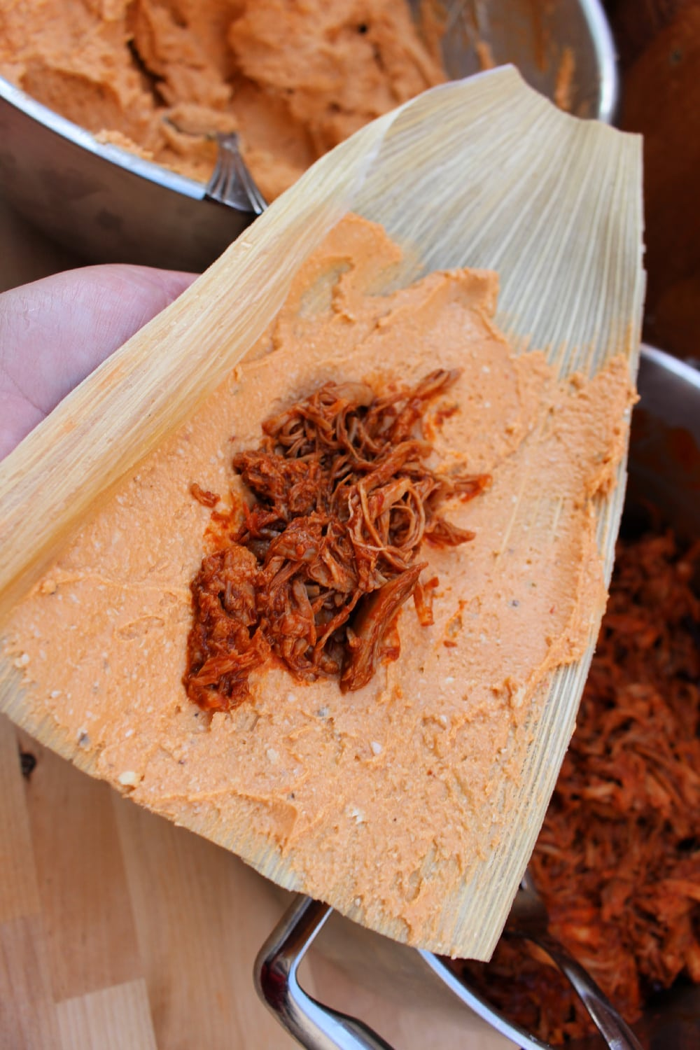 Pork in the center of the masa on a corn husk.