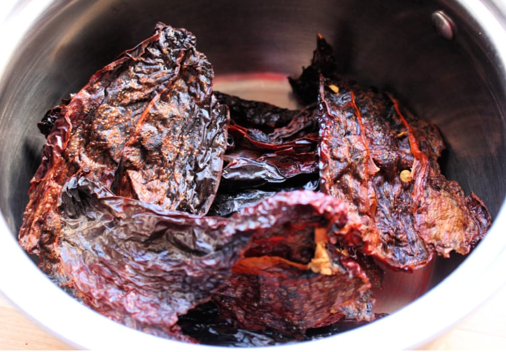 Dried chile ancho in a metal stock pot.