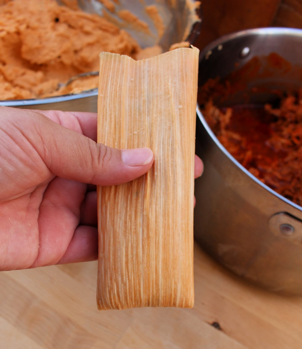 Hand holding a folded tamal and ready to cook.