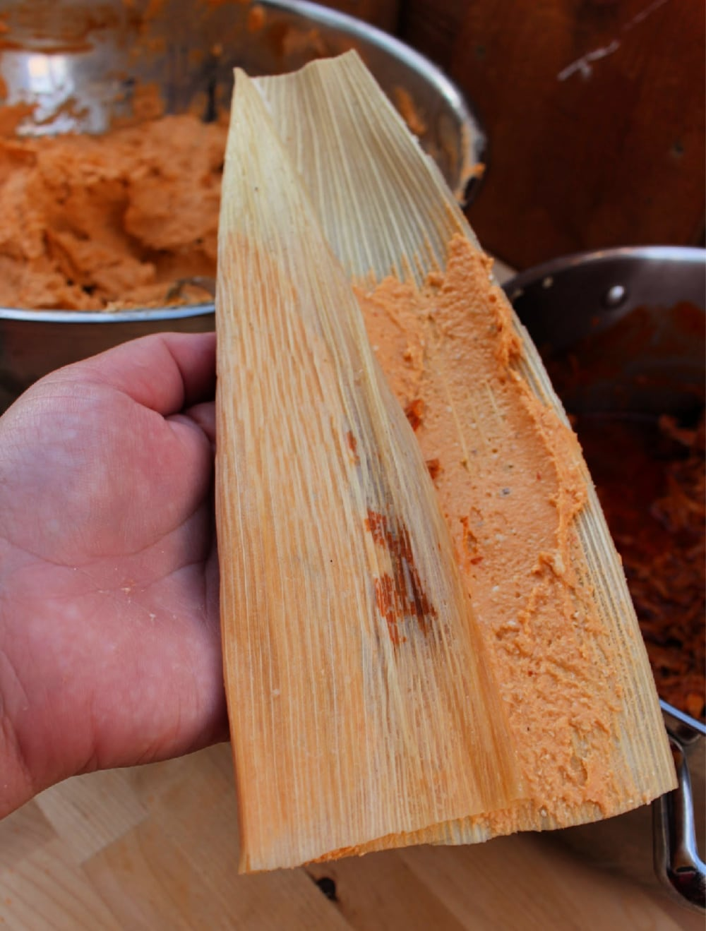 Hand holding a corn husk with one side of the husk folded in.