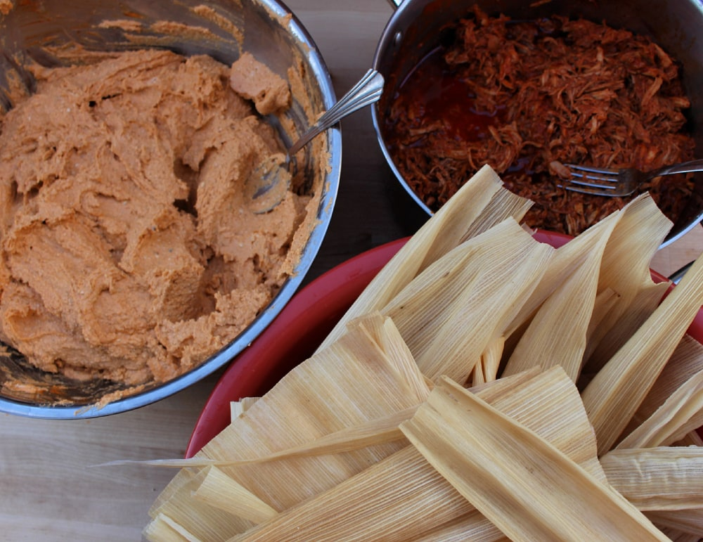 Corn husks, pork, and masa ready to assemble red pork tamales, or tamales de puerco rojos.