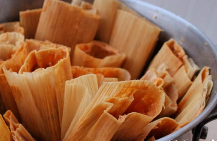 Pot of pork tamales with the open side up.