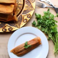Red Pork Tamales on decorative golden plate surrounded by forks and cilantro, and a single tamal on a white plate with a cilantro leaf on top.