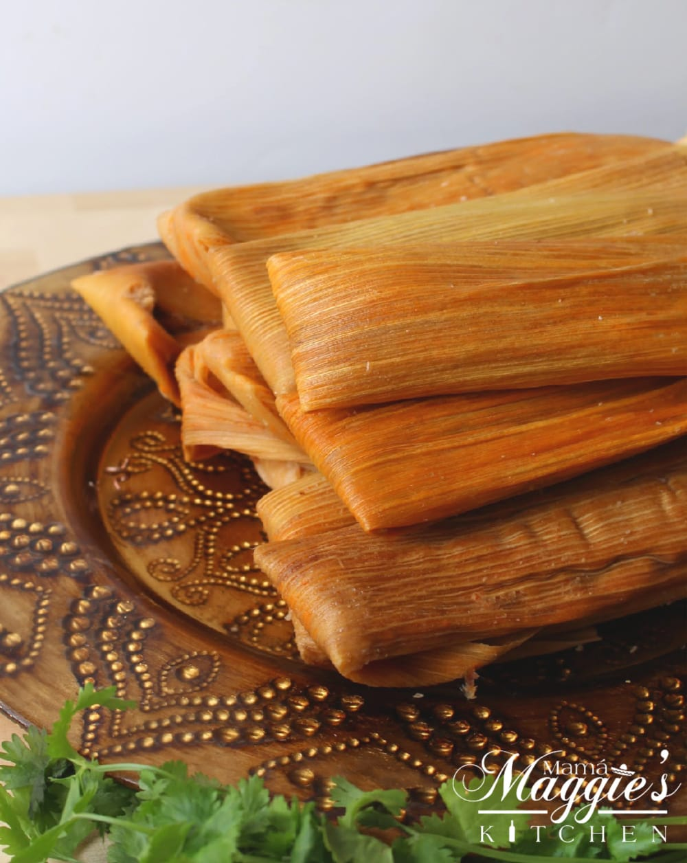 Red Pork Tamales on a decorative gold plate.