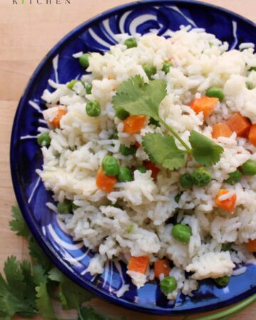 Arroz Blanco (or Mexican White Rice) on a decorative blue plate surrounded and garnished with cilantro leaves.