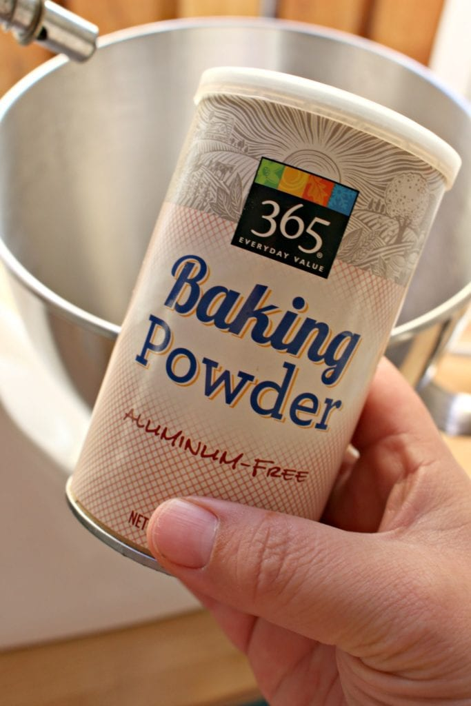 Hand holding a container of baking powder next to a mixing bowl.
