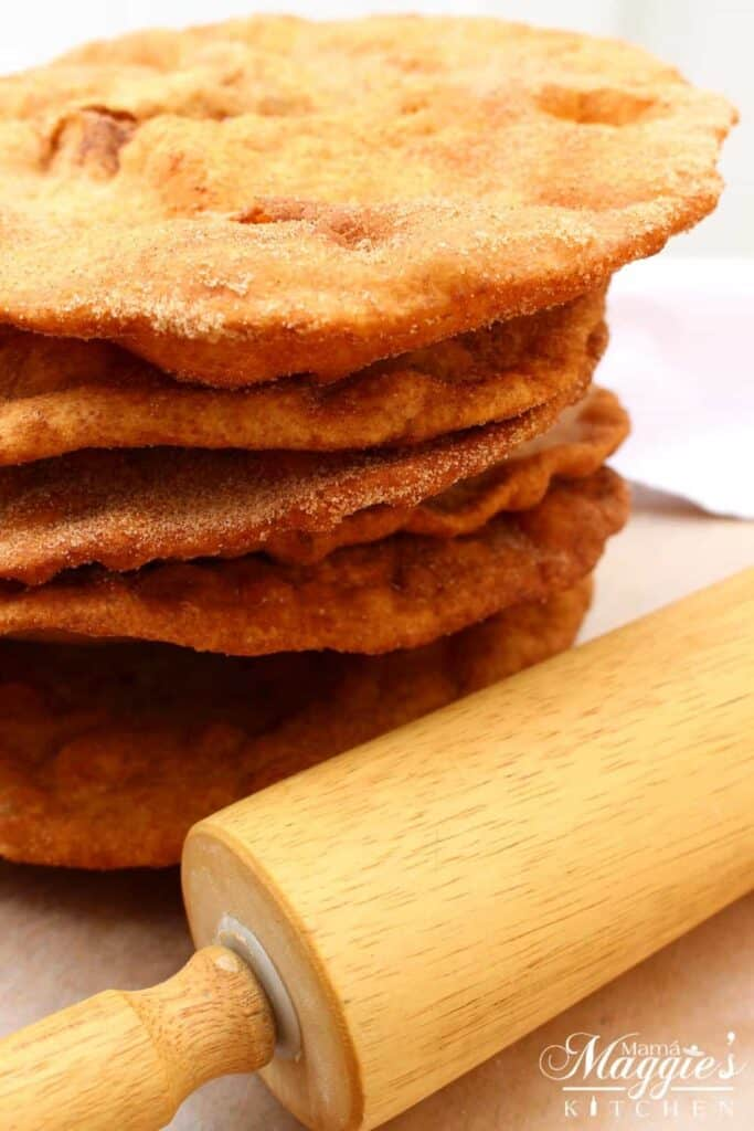 Buñuelos, or Mexican Fritters, stacked up next to a rolling pin.