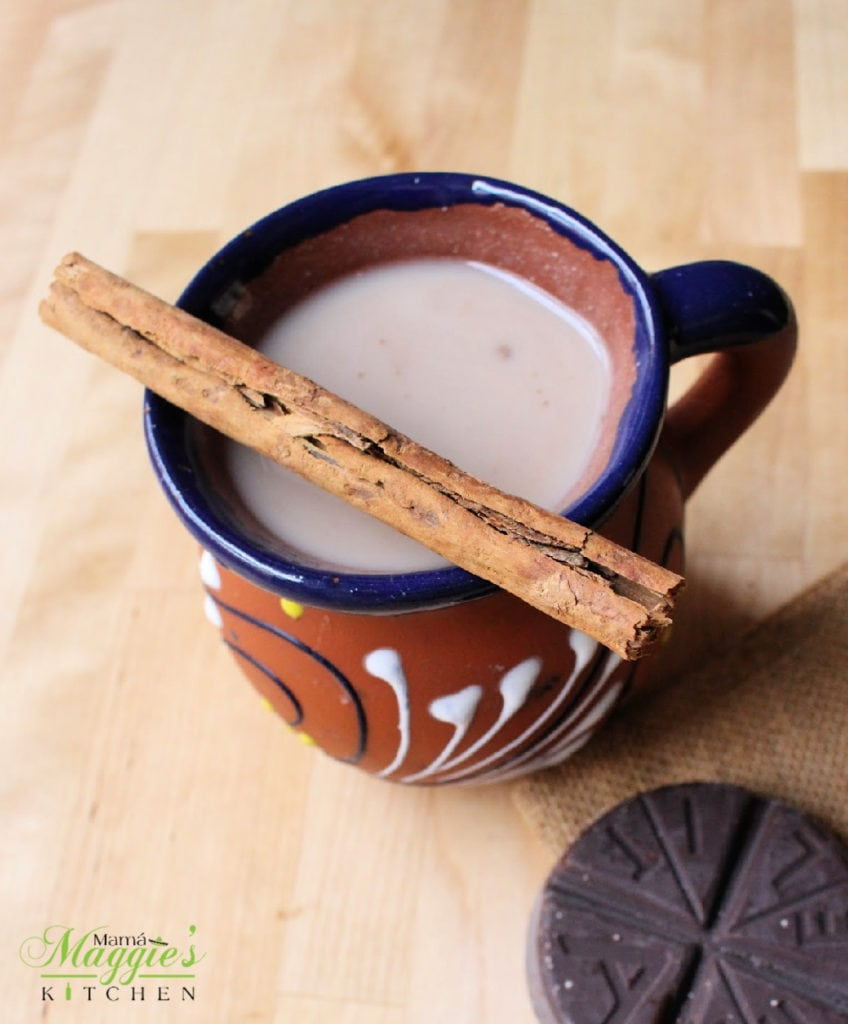 Champurrado in a decorative Mexican clay cup topped with a cinnamon stick next to a tablet of Mexican chocolate.