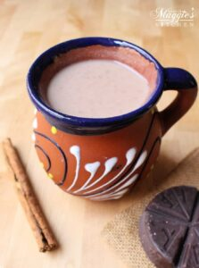 Champurrado in a decorative, clay Mexican cup surrounded by a cinnamon stick and Mexican chocolate tablet.