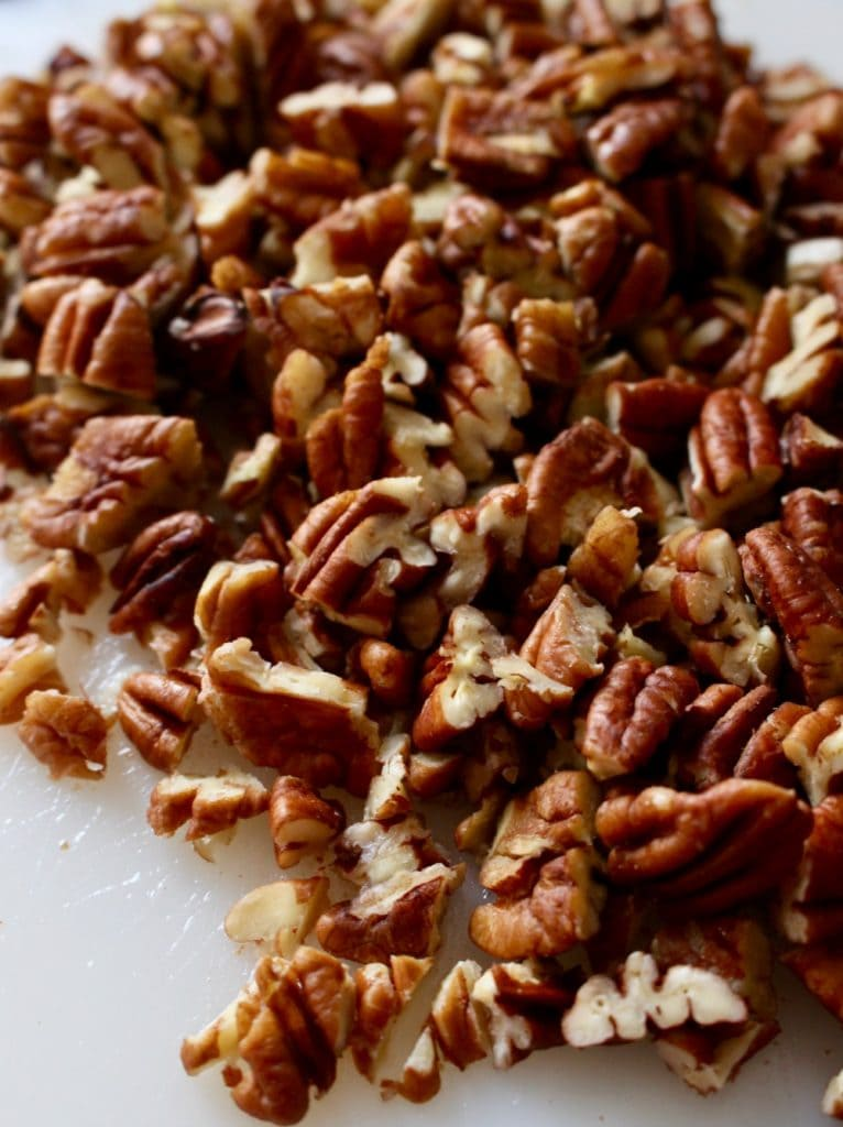 Chopped pecans on a cutting board.