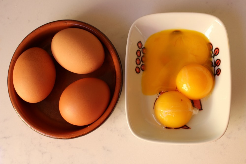 Three eggs in a clay bowl and three egg yolks in a small bowl.