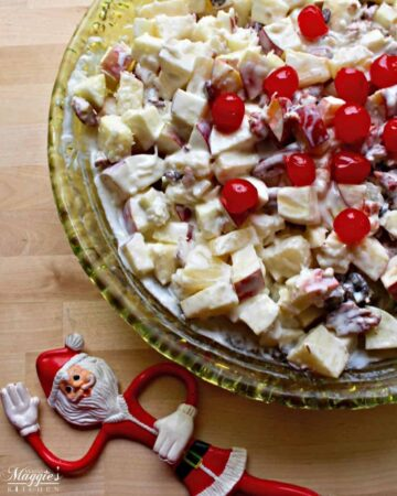 Ensalada Navideña (or Mexican Christmas Fruit Salad) in a green glass bowl topped with cherries and next to a toy Santa doll.