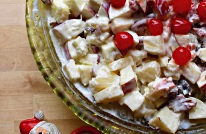Ensalada Navideña (or Mexican Christmas Fruit Salad) is a mixture of apples and other fruits covered in a dreamy and creamy dressing in a green, glass bowl next to a plastic Santa.