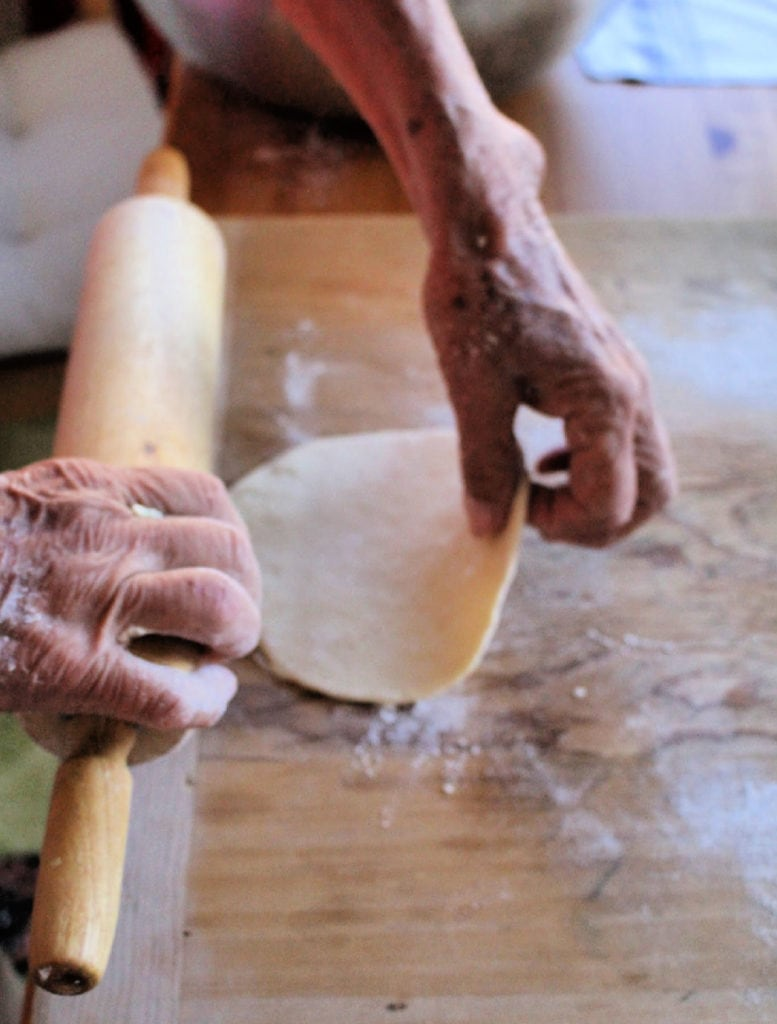 Hand holding a rolling pin and with the other hand flipping the rolled out dough.