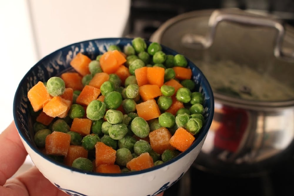A bowl with frozen peas and carrots over a black stove and stockpot.