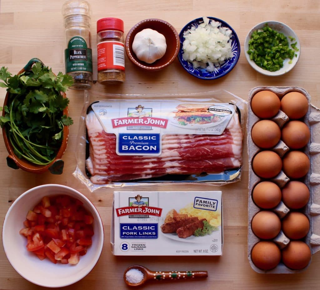 Ingredients for Mexican-Style Bacon, Sausage, and Eggs on a wooden surface.