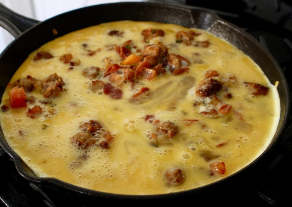 Eggs poured into a skillet with bacon and sausage.