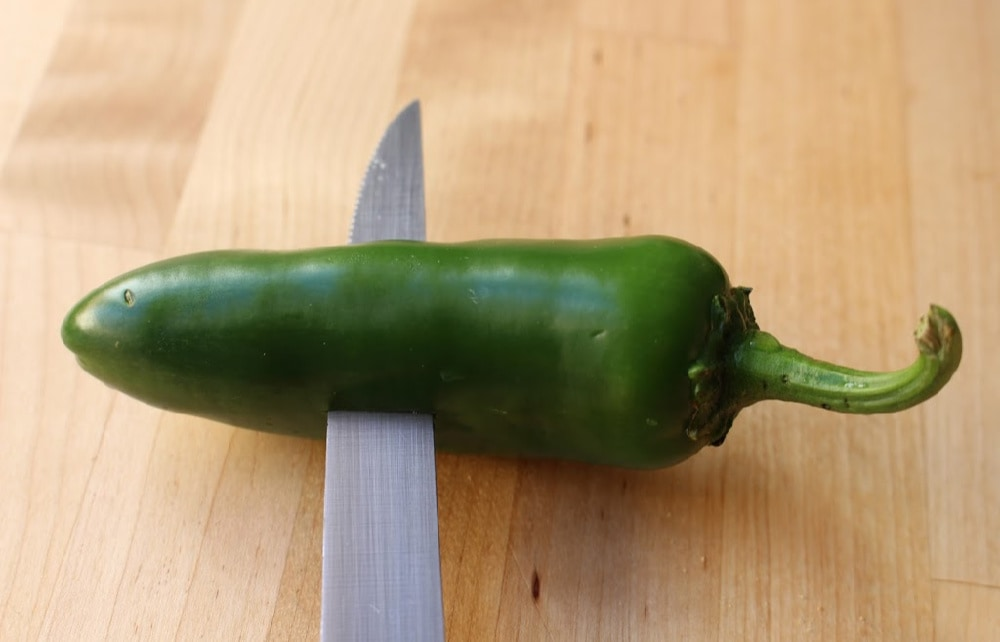 A knife making an incision in the center of the jalapeno on a wooden surface.