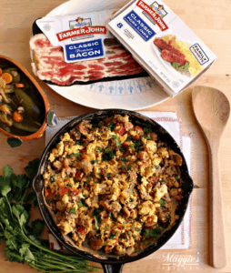 Mexican Style Sausage, Bacon, and Eggs surrounded by packages of Farmer Johns bacon and sausage and a wooden spatula.