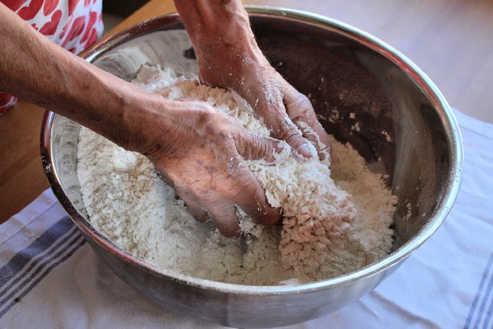 Hands mixing flour in metal bowl.