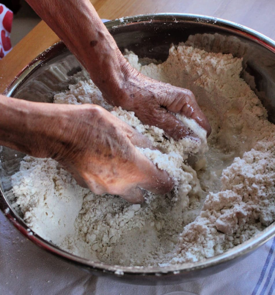 Hands mixing flour in a metal bowl.