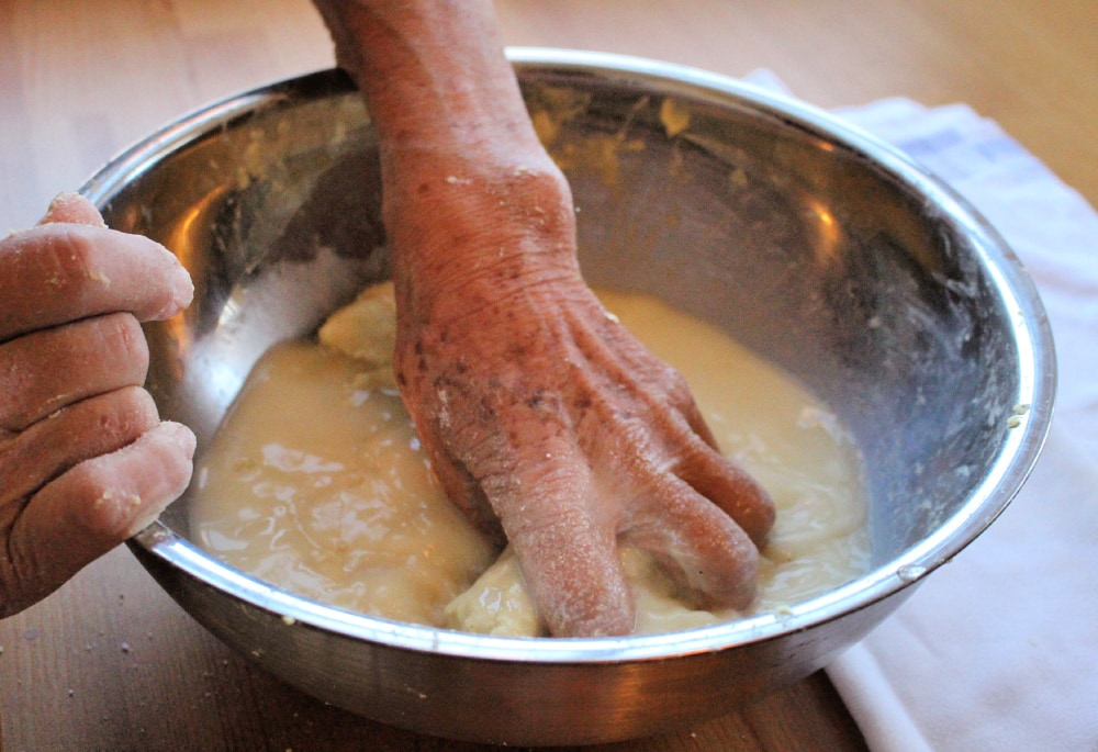 Hand in a metal bowl mixing masa and water.