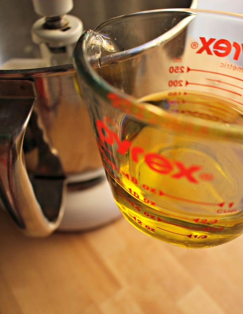 Measuring cup with olive oil next to the Kitchen Aid.