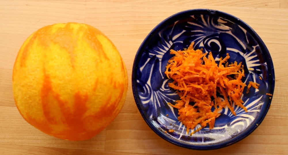 An orange without the zest and a blue plate with the orange zest.