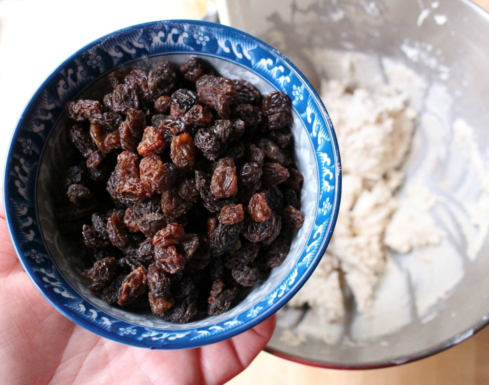 Hand holding a cup cup of raisins over the masa bowl.