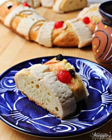 A slice of Rosca de Reyes (or Roscón de Reyes) on a decorative blue plate with the cake in the background.