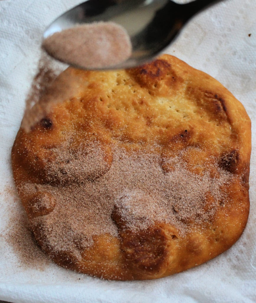 Spoon sprinkling sugar and cinnamon on the fritter.