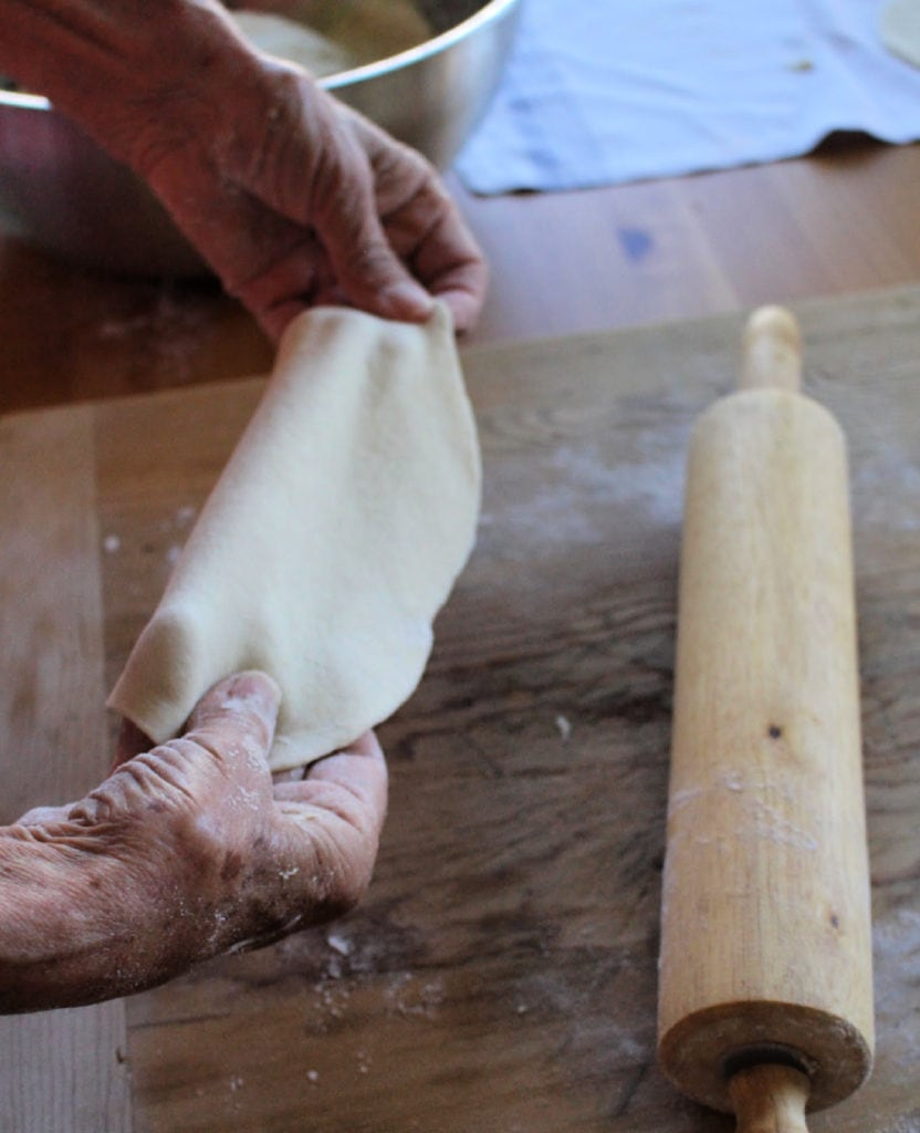 Hands stretching out the Buñuelos dough.