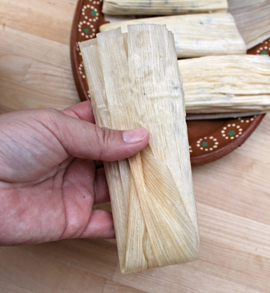 Hand holding a folded and fully assembled tamal.