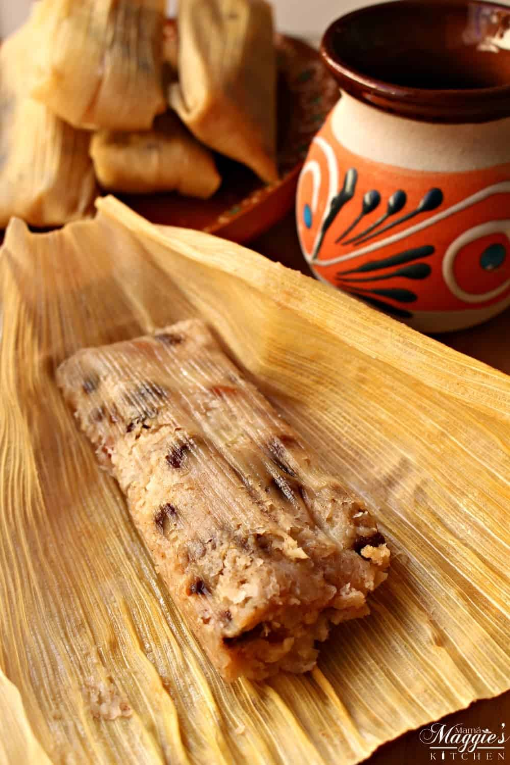 Tamales Dulces (Sweet Tamales) unwrapped but still in the corn husk surrounded by a pile of tamales and a decorative Mexican cup.