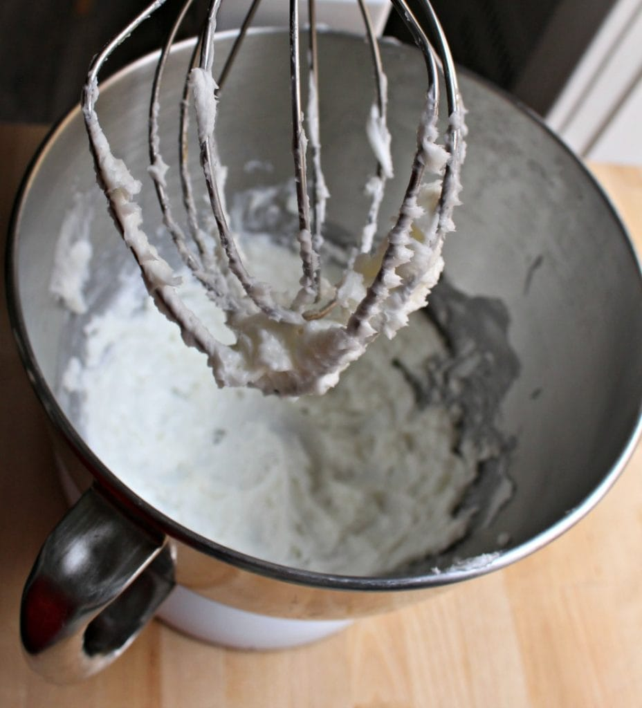 Whipped shortening in a Kitchen Aid stand with a whipping mixture full of fluffy shortening.
