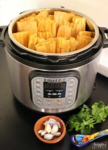 Instant Pot Pork Tamales stacked and ready to cook. Surrounded by cilantro and decorative Mexican kitchenware.