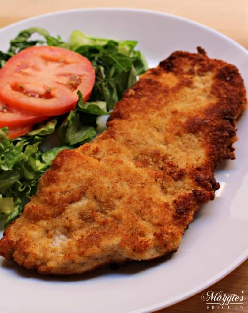 Milanesa de Pollo (or Chicken Milanese) on a white plate next to a green salad and slices of tomato.