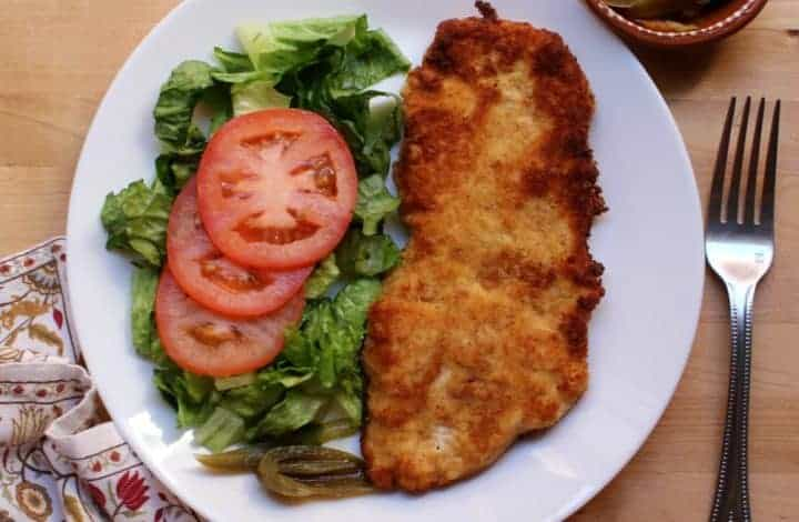 Milanesa de Pollo (Chicken Milanese) on a white plate next to a salad and surrounded by a decorative napkin and jalapeno slices and fork.