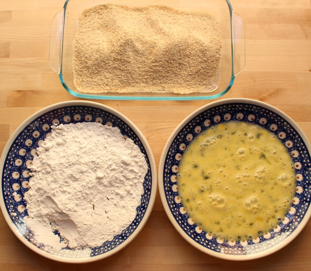 Two plates with egg and flour and one deep casserole dish with breadcrumbs on a wooden surface.
