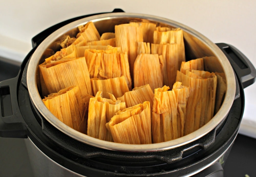 Tamales sitting open-side up inside the instant pot.