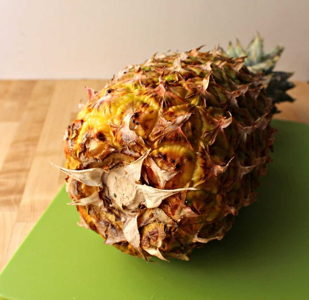 Pineapple turned on its side showing the bottom on a green cutting board.