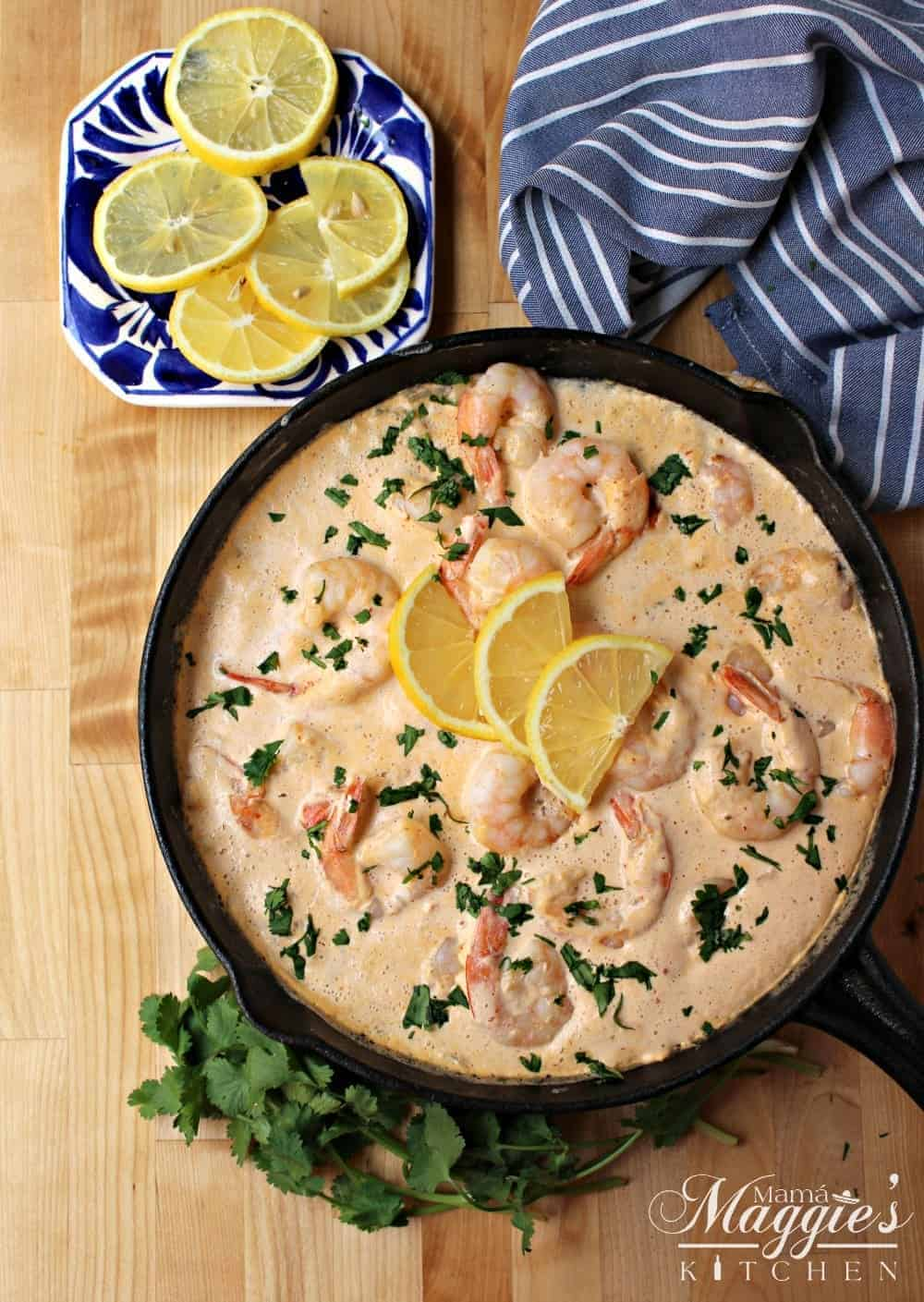 Camarones en Crema Chipotle in a black iron skillet topped with slices of yellow lemon and surrounded by a blue kitchen towel and green cilantro.