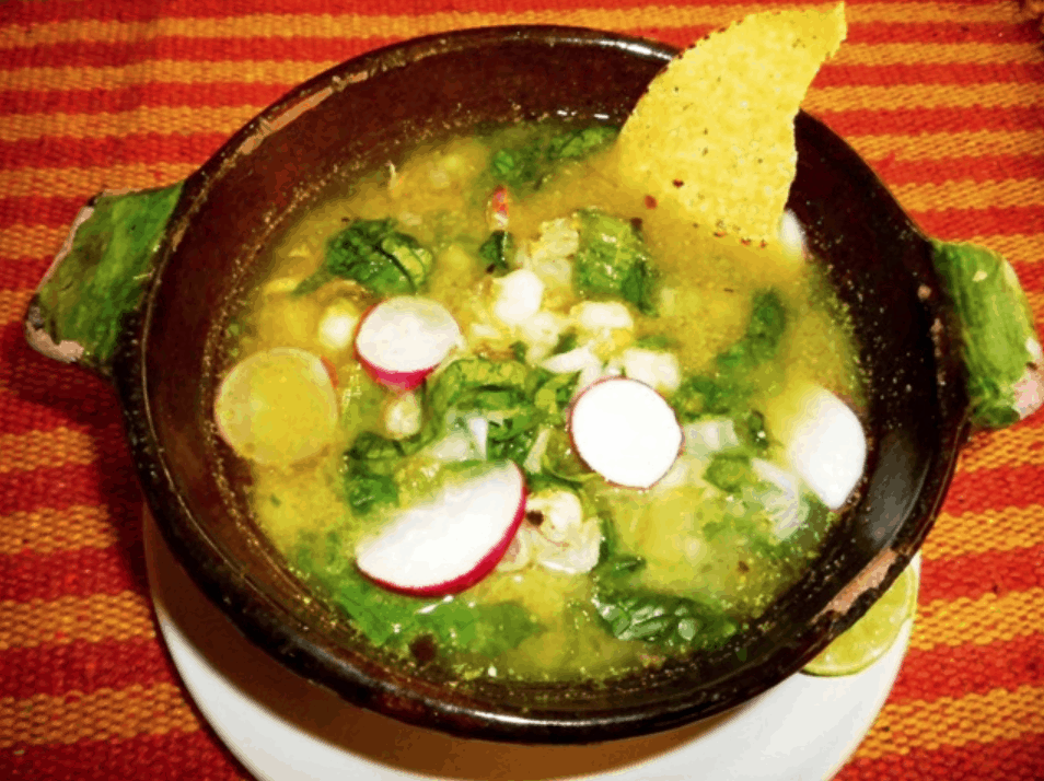 Green Pozole Guerrero Style in a dark brown bowl and topped with slices of radishes.