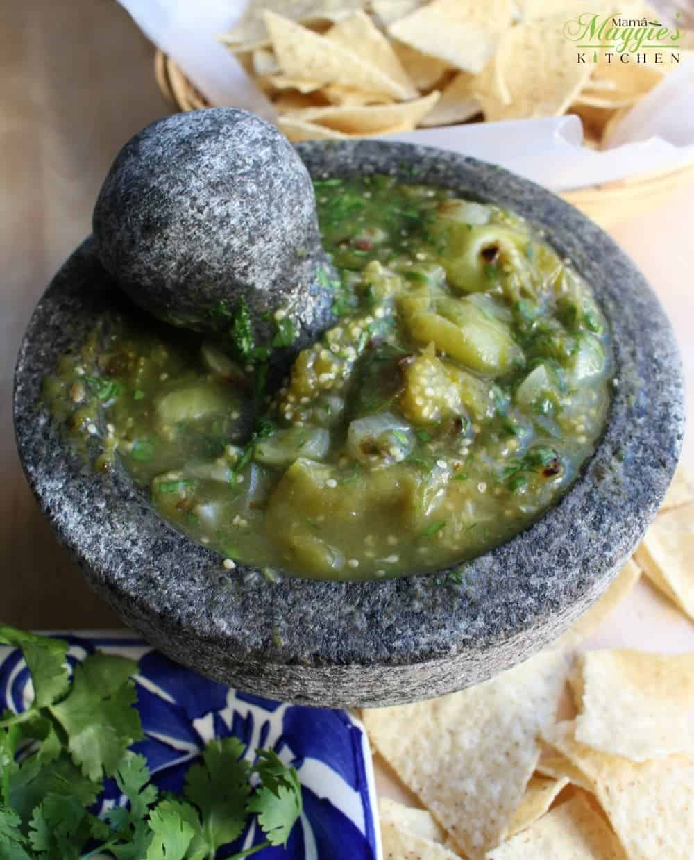 Molcajete Salsa Verde surrounded by corn tortilla chips and green cilantro.