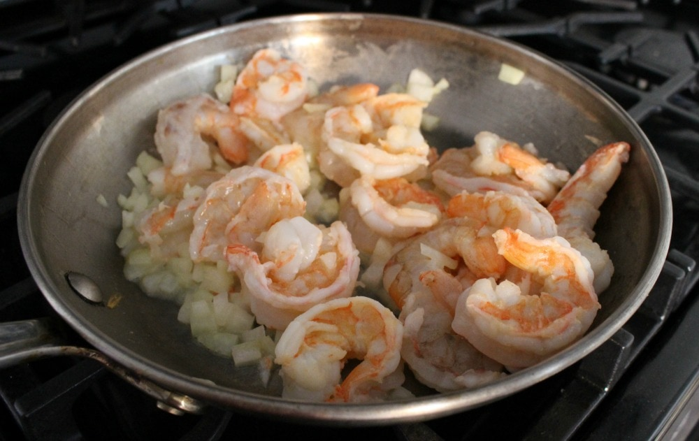 Shrimp and onion cooking in a metal skillet.