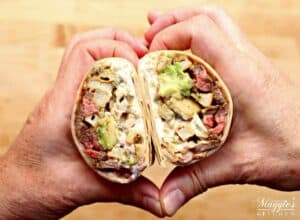 Hands making a heat shape with the California Burrito inside the heart.