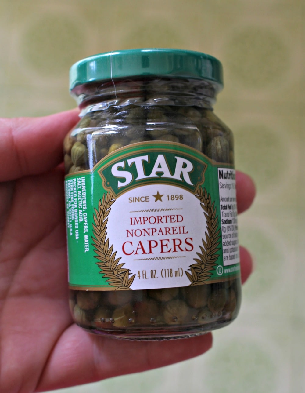 Hand holding a jar of capers